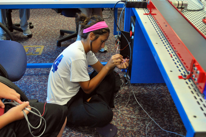 Evolving CTE Programs - Female Student Working on Wiring for Pegasus robot and tabletop mechatronics system as part of Amatrol robotics camp