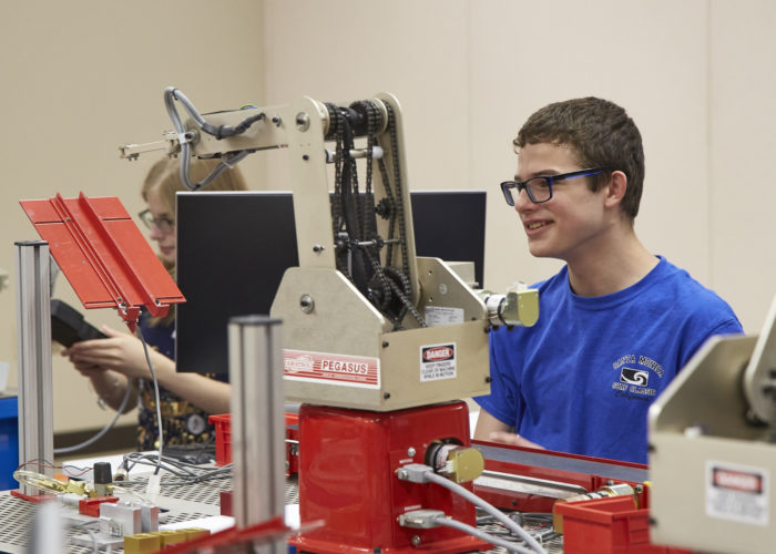 Male high school student working with Pegasus robot