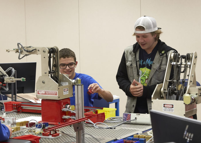 Evolving CTE Programs - Male high school students working on Pegasus robot at robotics camp